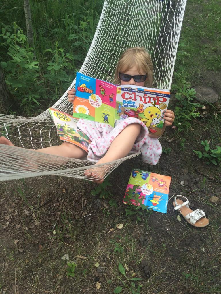 kira reading Chirp Magazine camping
