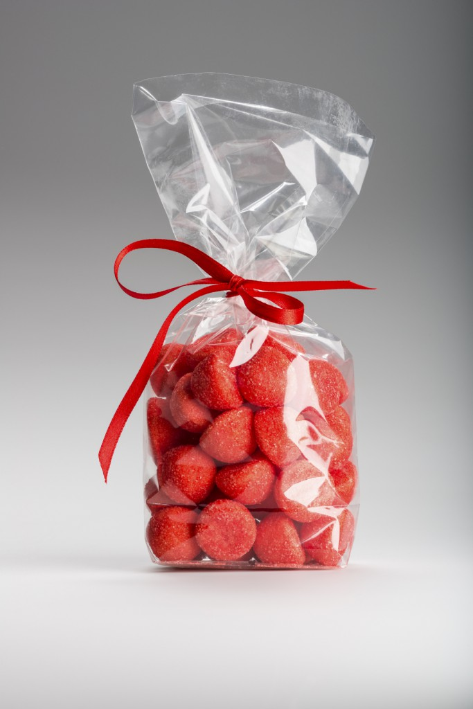 Beautiful and delicious acidulous strawberries bag with elegant red ribbon isolated on grey background. Shooting in studio.
