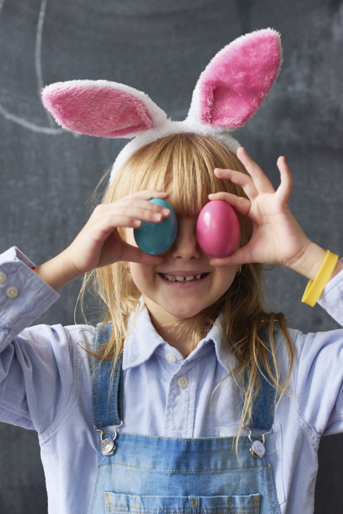 Little girl with Easter eggs on eyes